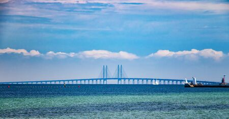 Oresund Bridge connects Denmark and Sweden. The bridge is a combined railway and motorway bridge. The North Sea has a beautiful turquoise blue color. There is summer time.