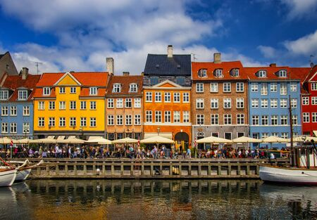 View of Nyhavn pier with color buildings, ships, yachts and other boats in the Old Town of Copenhagen, Denmark. Blue sky is in the background. There is summer time.