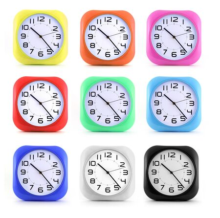 Set small alarm clocks in different colors on white background. Alarm clock serves to wake up early.