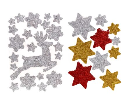 Set of glitter Christmas stickers isolated on a white background. They are white, gold and red stars and running Christmas reindeer. We can decorate gifts or Christmas cards or windows.