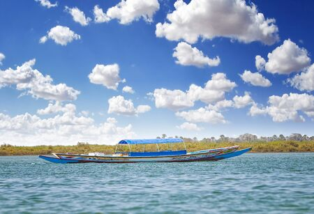 Traditional colorful wooden boat on the river in sea lagoon and a beautiful sky in the background, Africa, Senegal. It is summer. Stock Photo