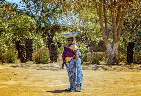 Goree, Senegal, APRIL 22, 2019: Unidentifed Senegal woman has a fruit basket on her head and wearing the typical colorful traditional Senegl clothes. It is summer time.