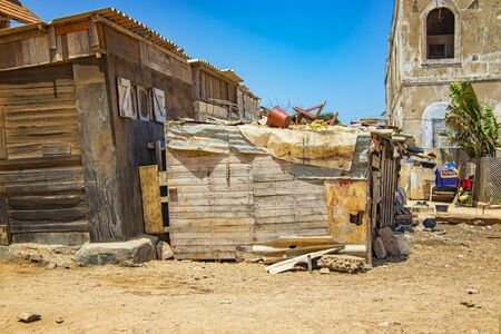 Una tipica baracca di legno sbriciolata sorge su un terreno polveroso nel mezzo di Goree, Seengal. È vicino a Dakar, in Africa. C'è disordine e lavaggio sul tetto. È un giorno di sole. Archivio Fotografico