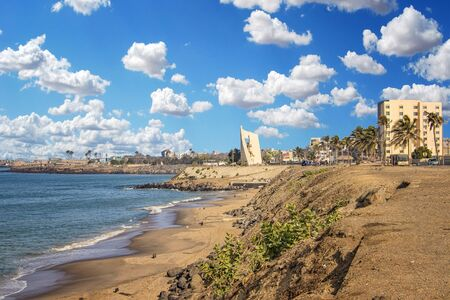 Views of the coastline of Dakar, Senegal, Africa. It is a beautiful long beach and in the background you can see buildings and palm trees and a beautiful blue sky. It is a beautiful sunny day.