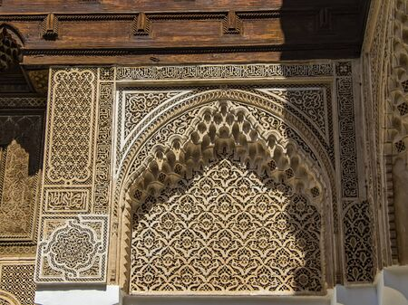 Detail of islamic building. It is an old architecture in the middle of the Moroccan city. There are white walls with wooden carved characters. There is summer time. It's a beautiful pattern.