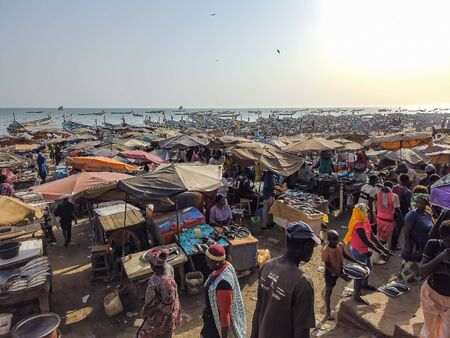 MBour, Senegal- April 25 2019: Unidentified Senegalese men and women at the fish market in the port city near Dakar. There are stalls selling and fishing boats everywhere. It is sunny day.