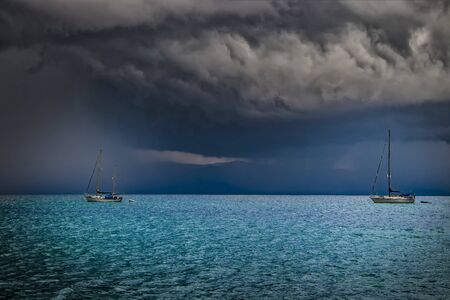 Two small yachts in sea with storm weather near Cagliari, Italy. In the distance it rains a lot and lightning falls. The clouds are gradually retracting and are black. It's summer.