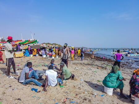 MBour, Senegal- April 25 2019: Unidentified Senegalese men and women waiting for the fishermen at the fish market in the port city near Dakar. There are stalls selling and fishing boats everywhere.