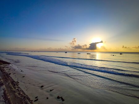 Beautiful sunrise on Diani beach on the Indian Ocean. It is a sunny morning in Kenya, Africa. There are small wooden boats on the water. The sky is blue.
