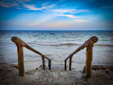 Stone stairs to the sea with wooden railing. It is on Diani beach in Kenya, Africa. Waves at high tide reach down to the stairs. It's sunset.