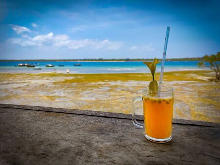 A cocktail of tropical fruits stands on a wooden railing. Low tide at Wasini island in Kenya, Africa. Wonderful view of the sea and small boats. It is a sunny day.