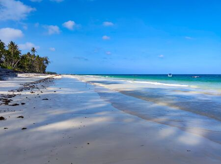 Tropical white sand beach at sunrise. Diani beach, Kenya. It is a beautiful long beach in Africa. It is a sunny day. Imagens - 145109593