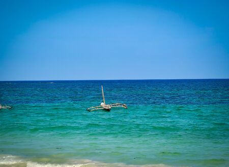 Typical Swahili wooden canoe on the sea at Diani beach, Kenya. It is a beautiful long beach in Africa. It is a sunny day. Imagens