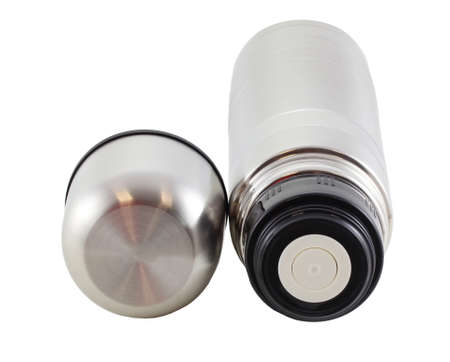 Stainless steel flask lies isolated on a white background. It can be used for hot tea or coffee. The lid is unscrewed. It serves as a mug.