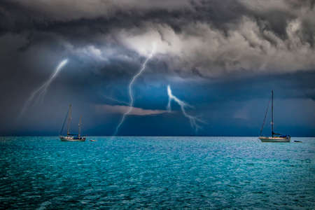 Yachts are at sea in a storm. Lightning flashes from the sky into the water. It's in Sardinia, Italy. It's raining from black clouds. It's summer. Imagens