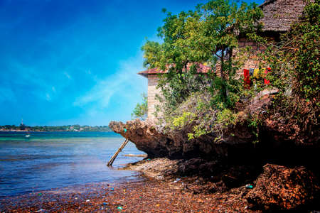 A small house on a cliff above the sea on the island of Kisite in Kenya. It's the Indian Ocean. A ladder leads into the water. There is a sea reservation around. It is a beautiful day. Imagens - 155715117