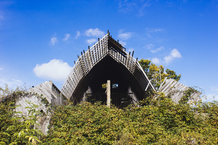 run down: Old run down symmetrical barn with overgrowth Stock Photo