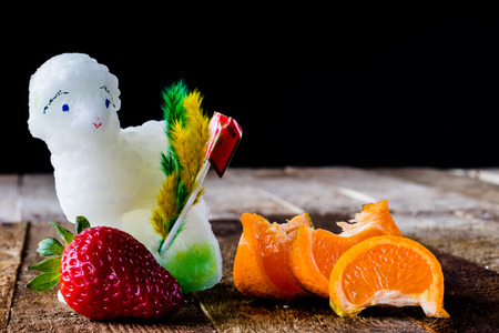 Mandarin, strawberry and chocolate on an old wooden table in an old kitchen on a black background