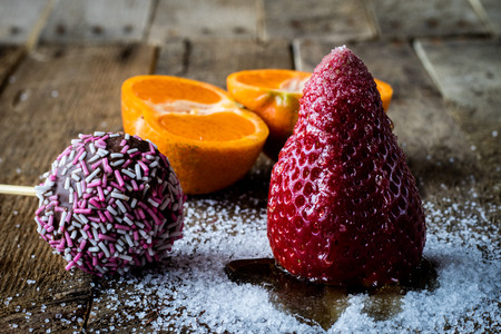 citrons: Mandarin, strawberry and chocolate on an old wooden table in an old kitchen on a black background