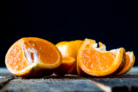 citrons: Mandarin on an old wooden table in an old kitchen on a black background