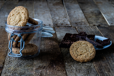 gingerbread: Milk and chocolate cookies on an old wooden table, black background Stock Photo