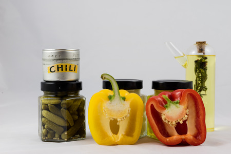 Red and yellow peppers, preserves and olive oil in the pantry Imagens