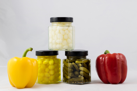 Red and yellow peppers, preserves and olive oil in the pantry Stock Photo