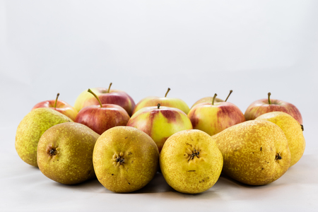 Delicious, delicious ripe apples and pears on a white isolated background