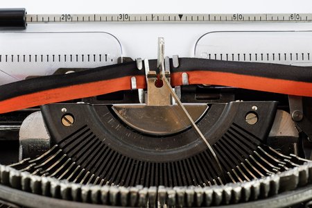 Old, well-worn typewriter on a white isolated background. Sheet of paper.