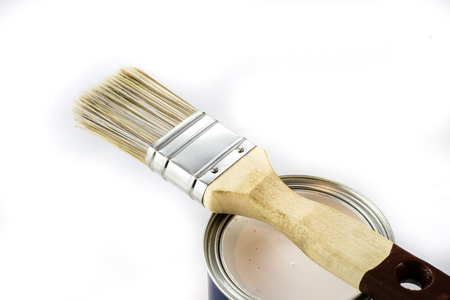 oil can: Paintbrush lying on tin can, white isolated background