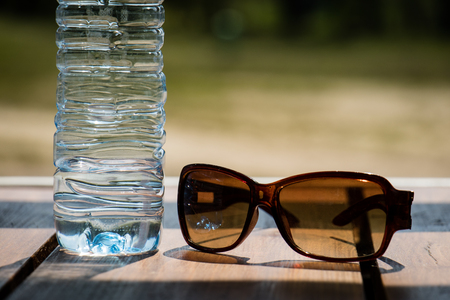 near beer: Water bottle and sunglasses on the table on a sunny day.