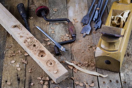 antique furniture: Old carpentry, carpentry workshop, drilling in a piece of wood.