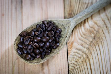 molinillo: Granos de café en un frasco y cuchara de madera, mesa de madera, fondo negro Foto de archivo