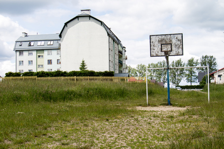 snatched: Old basketball court, basket, snatched netting against the sky and clouds