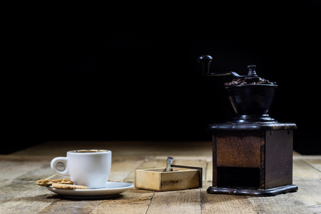 Freshly brewed coffee in mugs on a wooden table with a mill on a black background Zdjęcie Seryjne