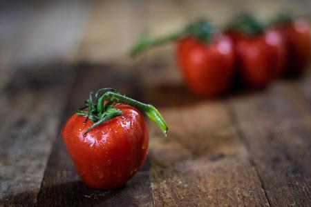 Rosa on tasty Italian tomatoes, wooden table, black background