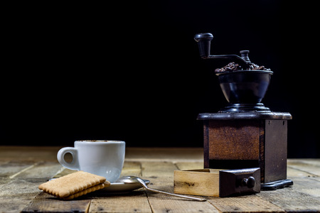 Freshly brewed coffee in mugs on a wooden table with a mill on a black background Stock Photo