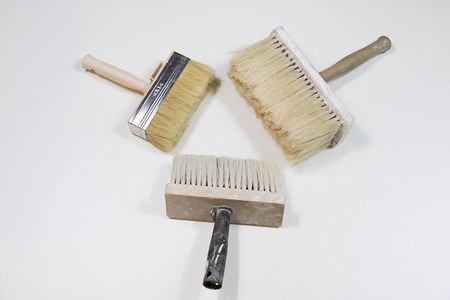 home decorating: Roller and paint brush on a white background. Old painting tools