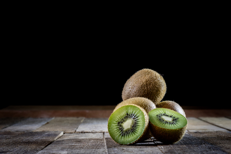 Kiwi in the old kitchen on a wooden table. Black background.
