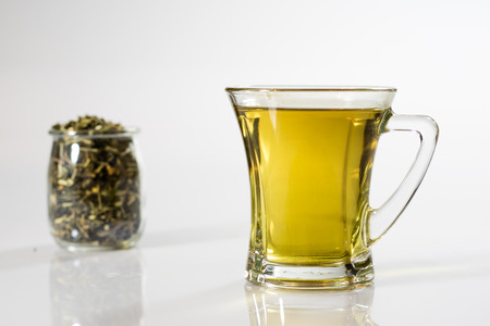 Tea in a glass on a white background. Green or fruit tea. Glass of white glass