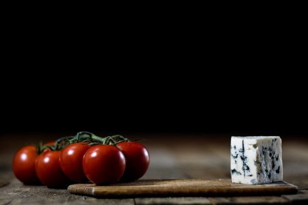 Lekkere landbrood en olijfolie in een glazen fles. Zwarte achtergrond en houten tafel. Stockfoto