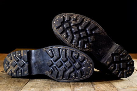 Old black Polish military boots on a wooden table. Black background. Reklamní fotografie