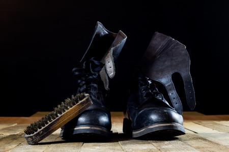 Old black Polish military boots on a wooden table. Black background. Imagens