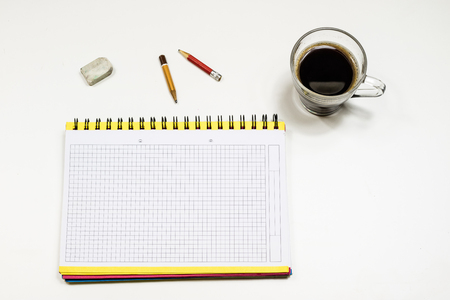Coffee and sketchbook for drawings. White table. Isolated background. White background. Stock Photo