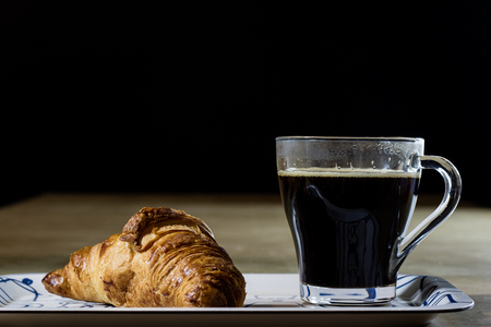 Fresh hot coffee and breakfast on the tray. Wooden table, black background. Stock Photo