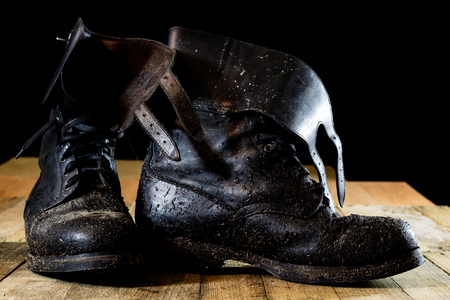 Muddy old military boots. Black color, dirty soles. Wooden table. Black background