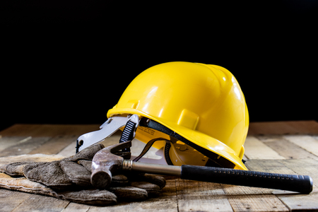 Yellow helmet and carpenter tools. Carpenter and old wooden table. Black background Stock Photo