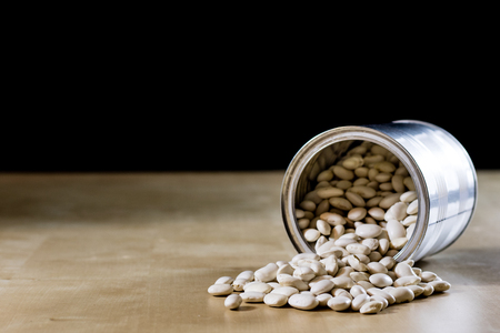 Delicious beans in a metal jar on a wooden kitchen table. Black background. Stock Photo