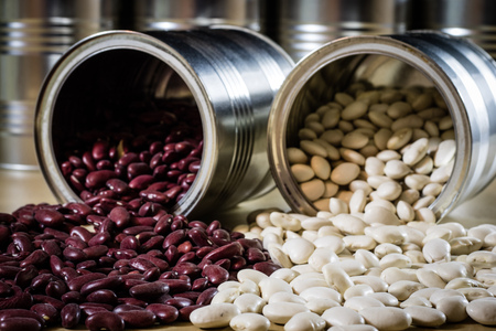 Delicious beans in a metal jar on a wooden kitchen table. Black background. Banque d'images