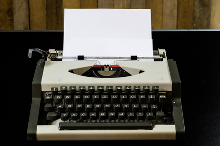 bureaucrat: typewriter on the black table. White blank card. Wall of rough boards. black background